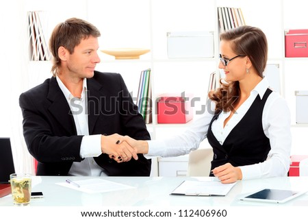 Business woman and businessman shaking hands at the meeting in the office. - stock photo