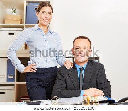 Business woman and happy man together at a desk in their office - stock photo