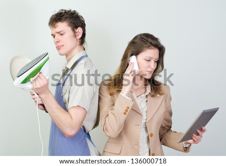 Business woman and her husband doing housework - stock photo