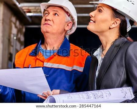Business woman and man in builder helmet indoor. - stock photo