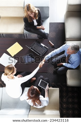 Business woman and senior business man shaking hand while sitting at business meeting. - stock photo