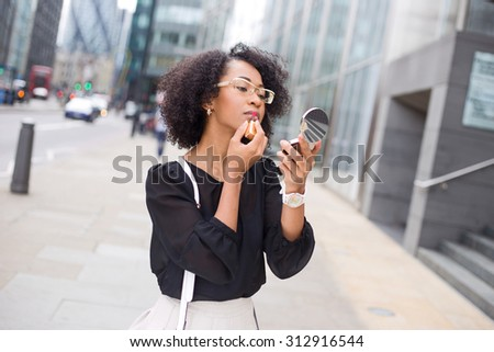 business woman applying lipstick in the street - stock photo