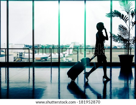 Business woman at Airport - Silhouette of a passenger - stock photo