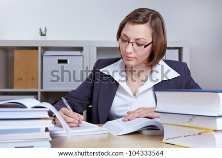 Business woman at her desk in the office doing research with books - stock photo