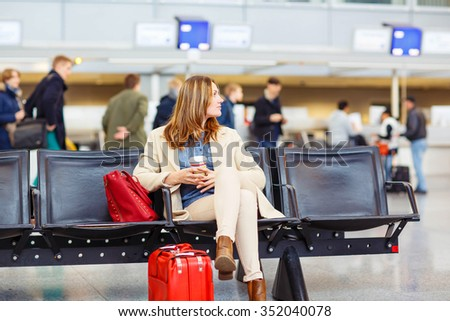 Business woman at international airport sitting and drinking coffee in terminal. Upset passenger waiting. Canceled flight due to pilot strike. - stock photo