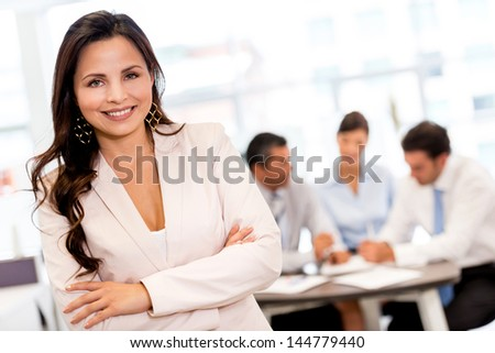Business woman at the office looking very happy and smiling - stock photo