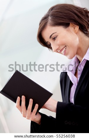 Business woman at the office reading a book and smiling - stock photo