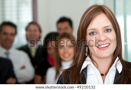 Business woman at the office with a group behind her