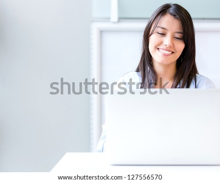 Business woman at the office working on a laptop - stock photo