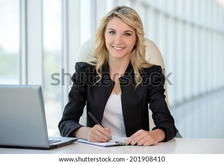Business woman at the office. Young beautiful business woman at work in his office - stock photo