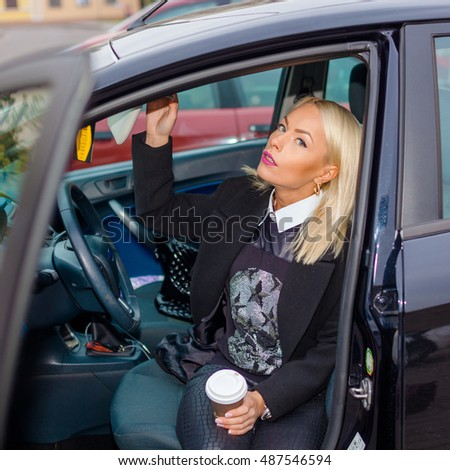 business woman at the wheel in the car with a cup of coffee. Young attractive positive Hipster girl behind the wheel with a cup of coffee