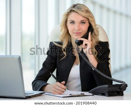Business woman at work. Confident young business woman talking on the phone while sitting at her working place - stock photo