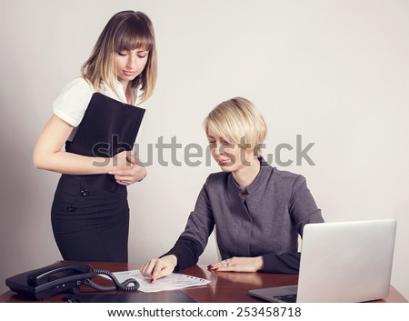 Business woman at work. Woman in the office. Two business woman working in the office. Work . checking and signing of accounting and tax records.
