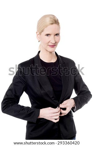 Business woman buttons up her jacket - stock photo