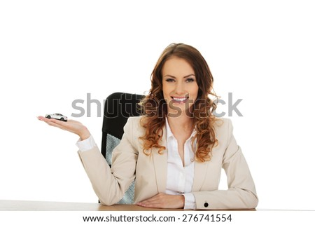 Business woman by a desk holding a toy car. - stock photo