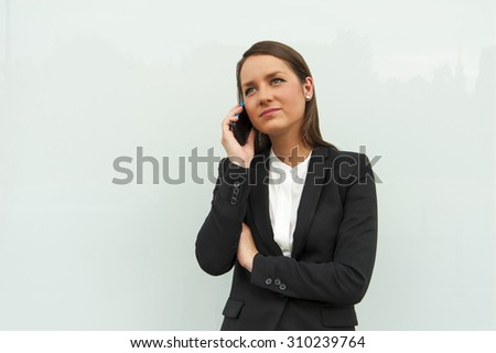 Business woman by the glass wall in the city talking by phone. - stock photo