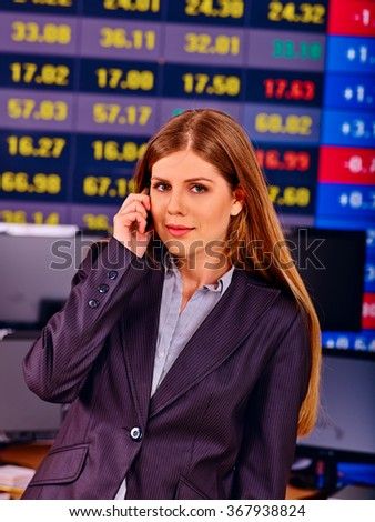 Business woman calling by phone with  stock exchange board on background .