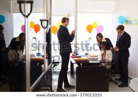 Business woman celebrating birthday and doing a party with colleagues in her office. A friend with mobile phone takes pictures of her blowing out clandles on birthday cake. Wide shot - stock photo