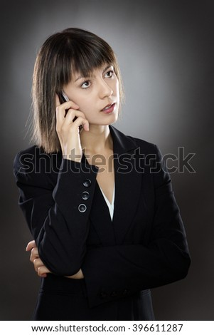 business woman chatting on a mobile phone low key lighting shot in the studio on a gray background