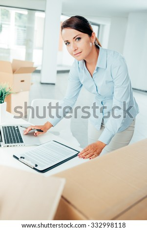Business woman checking an office relocation list on a clipboard and using a laptop, cardboard boxes on foreground - stock photo