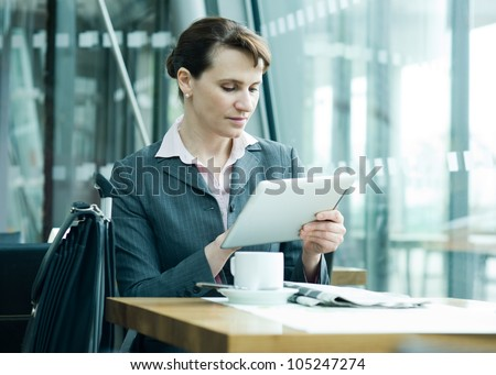 Business woman checking new on digital tablet at the airport business lounge - stock photo