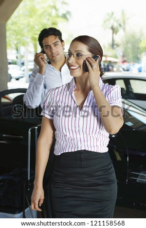 Business woman communicating on mobile phone with coworker and car in the background - stock photo