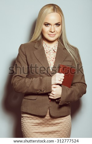 Business woman concept. Portrait of elegantly dressed young gorgeous blonde woman holding leather notebook, posing over golden background. Smart casual style. Studio shot - stock photo