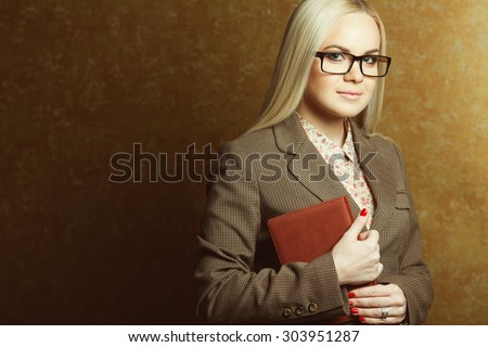 Business woman concept. Portrait of elegantly dressed young gorgeous blonde woman in trendy eyewear holding leather notebook posing over golden background. Smart casual style. Copy-space. Studio shot