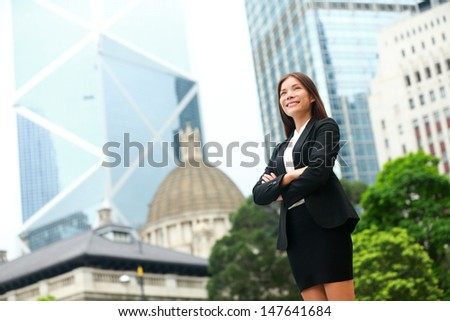 Business woman confident outdoor in Hong Kong standing proud in suit cross-armed in business district. Young multi-ethnic Chinese Asian / Caucasian female professional in central Hong Kong. - stock photo