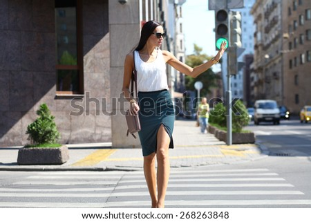 Business woman crossing the road outside in sunny weather