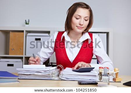 Business woman doing a tax audit in the office with files and calculator - stock photo