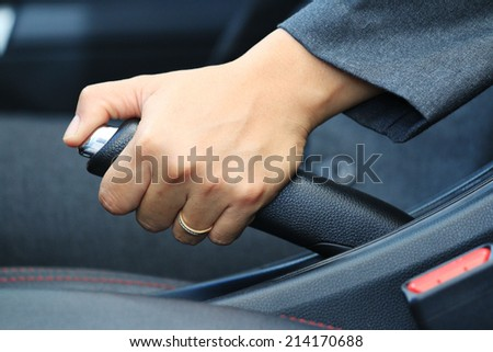 Business woman driver pulling the hand brake in car, in car background. - stock photo