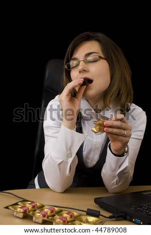 Business woman eating a chocolate