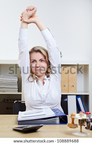 Business woman exercising her back in the office - stock photo
