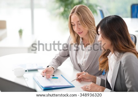 Business woman explaining something to her Vietnamese colleague