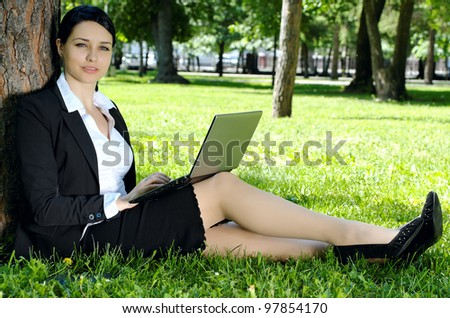 Business woman exploring internet using laptop in the park during rest - stock photo