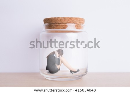 business woman feel unhappy and imprisoned in jar with white wall background, great for your design or text, asian - stock photo