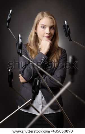 business woman getting annoyed with the number of selfie stick around her - stock photo