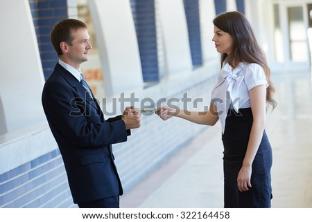 business woman gives money to businessman