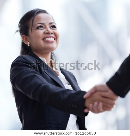 Business woman giving a handshake and smiling