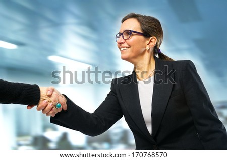 Business woman greeting a visit to her office with a handshake - stock photo