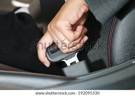 Business woman hand fastening a seat belt in the car. - stock photo