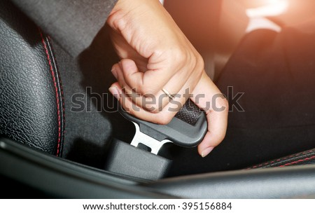 Business woman hand fastening a seat belt in the car.