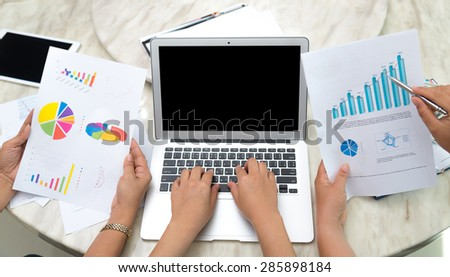 Business woman hand typing on laptop keyboard with Financial charts on the table - stock photo