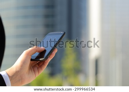 Business woman hand wearing suit texting on he smart phone with office buildings in the background in a sunny day - stock photo