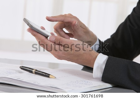 Business woman hand with pen make write notes in notebook and mobile smart phone. - stock photo