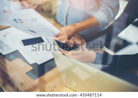 business woman hand working on smart phone and laptop computer and business graph information diagram on wooden table with window reflection at office.