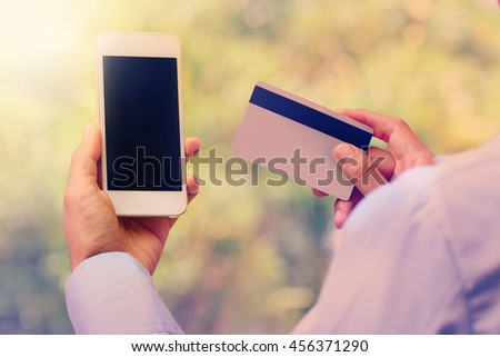 Business woman hands holding smartphone and credit card on nature vintage background.