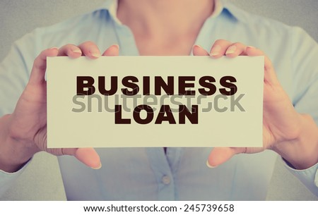 Business woman hands holding white card sign with business loan text message isolated on grey wall office background. Retro instagram style image - stock photo