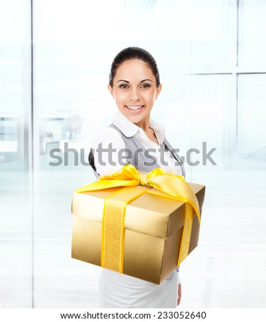 Business woman happy smile hold golden gift box in hands. Businesswoman in modern office - stock photo